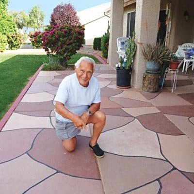 older man kneeling on patio