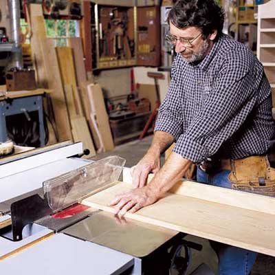 man using table saw in workshop