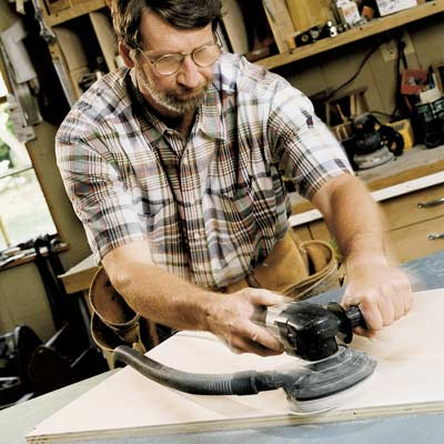 man using random orbit sander