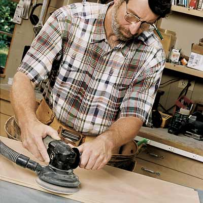 man sanding flat surface with random orbit sander