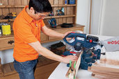 man sawing board with miter saw