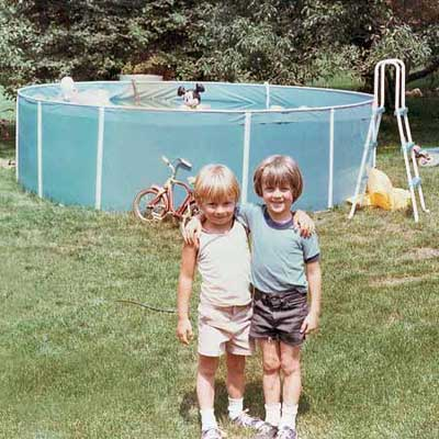 young boy and girl standing in front of above ground pool