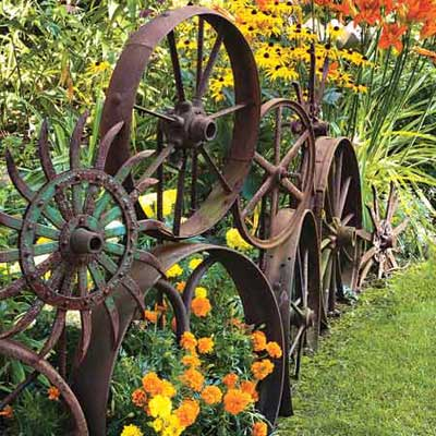 old metal wheels serve as backdrops for planting beds