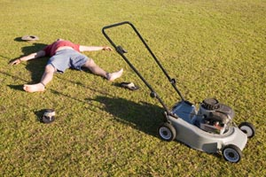 man lying next to lawn mower in yard
