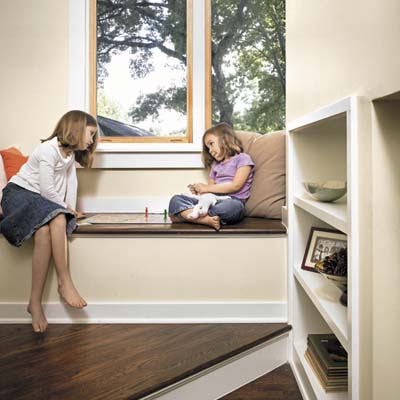two girls sitting in a window seat in sustainable home in Austin
