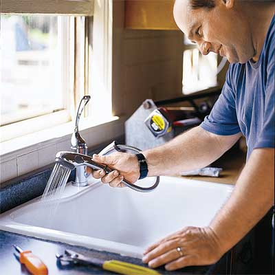 person testing a newly installed kitchen faucet