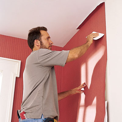 man applies wallpaper to a wall