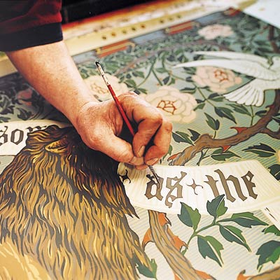 Arts and Crafts-style Lion and Dove frieze wallpaper being touched up by hand