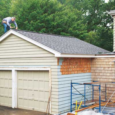 man installing shingles on gabled roof