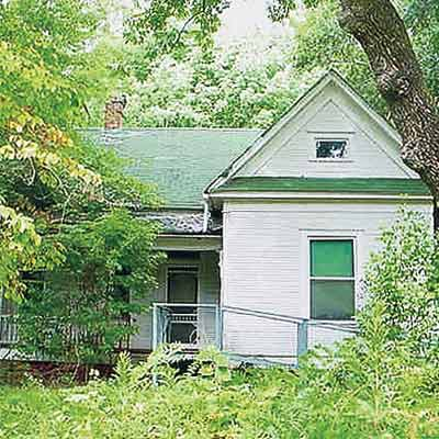 folk victorian house hidden with overgrown brush