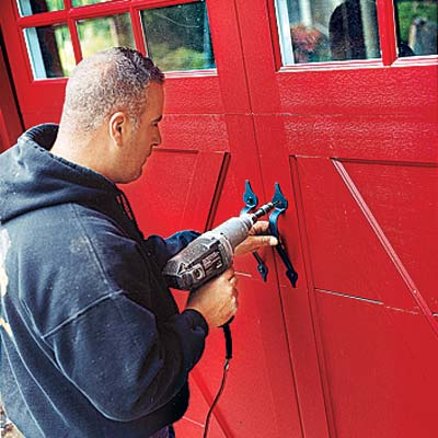 man repairing garage door with drill