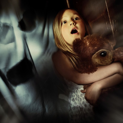 Frightened girl holding a teddybear
