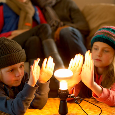 Family huddled around heat lamp