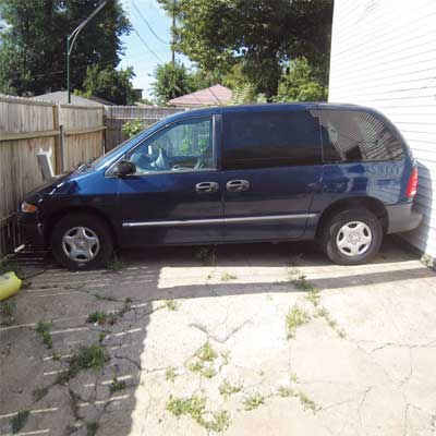 mini van parked between house and fence with no room to either end