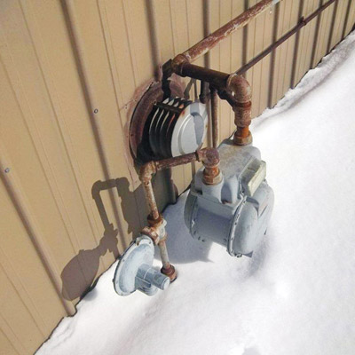 Gas wall mounted space heater and gas meter on side of house