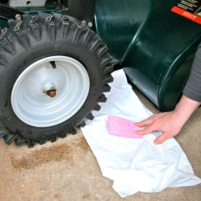 hand putting sponge under lawn mower to catch oil leak