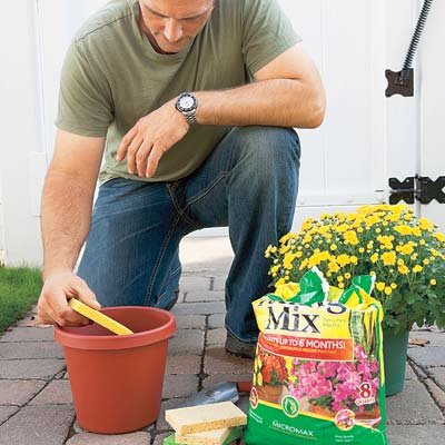 man placing sponges in bottom of planter