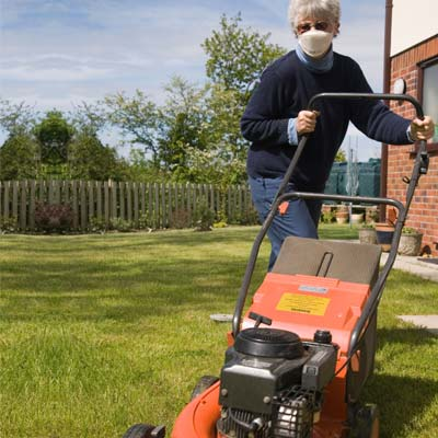 woman with a mask mowing the lawn