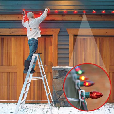 Man hanging christmas lights on home exterior