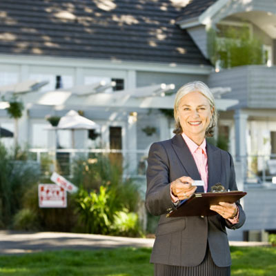 real estate broker handing out business card in front of house