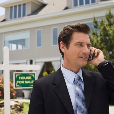 real estate broker talking on cell phone in front of house for sale