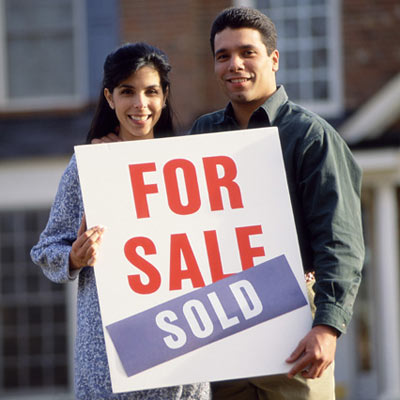 couple holding sold house sign on front lawn