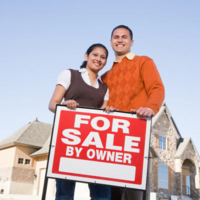 couple standing in front of for sale by owner sign