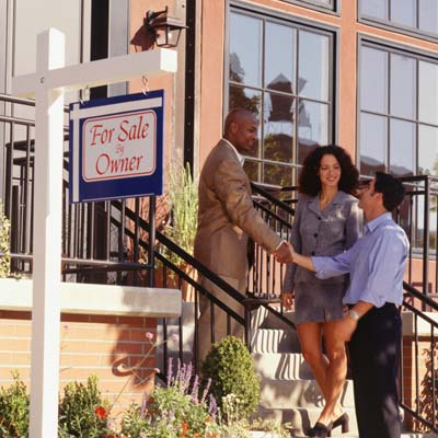 couple meeting real estate broker at rowhouse with for sale by owner sign