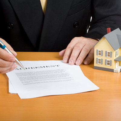 man holding home agreement and pen for signing