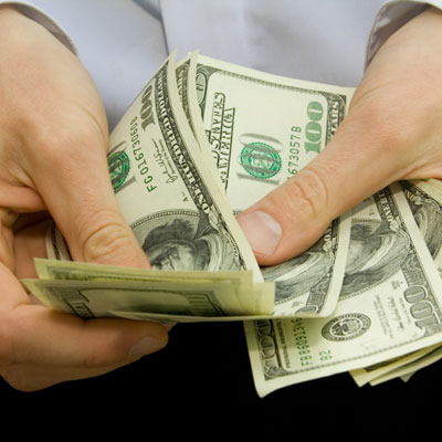 man's hands holding one hundred dollar bills