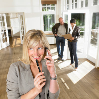 real estate agent on cell phone smiling with couple in background