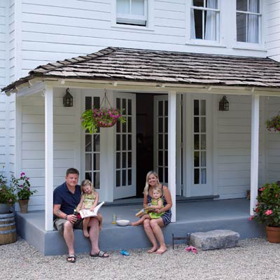 family sitting on remodeled farmhouse porch