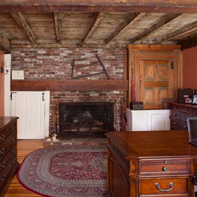 exposed-beam ceilings and brick fireplace surround in the study of the bedford house before this old house remodel