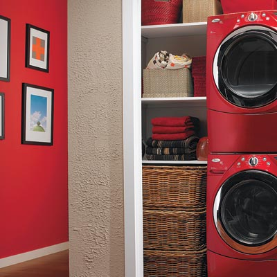 laundry room hidden in hall closet with red stackable washer and dryer and red accent wall
