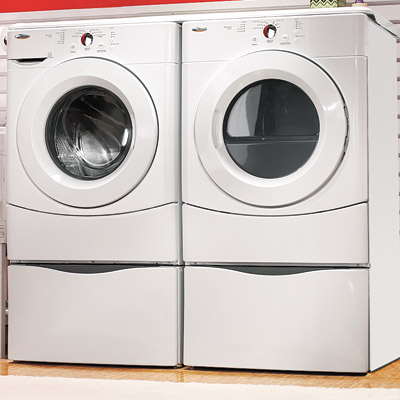 laundry room in garage with washer and dryer pedestals
