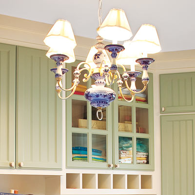 home office laundry room with sage green cabinetry and blue chandelier light