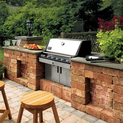 countertops on both sides of a grill in this beautifully designed outdoor kitchen