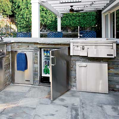 a sink and appliances installed with a grill in this beautifully designed outdoor kitchen