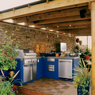 a pergola built above this beautifully designed outdoor kitchen