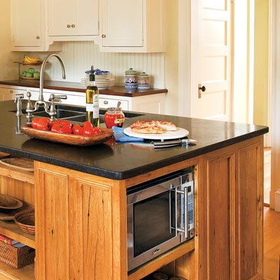 a kitchen island with built-in shelves for appliances
