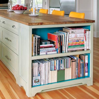 a kitchen island with open shelves for cookbooks