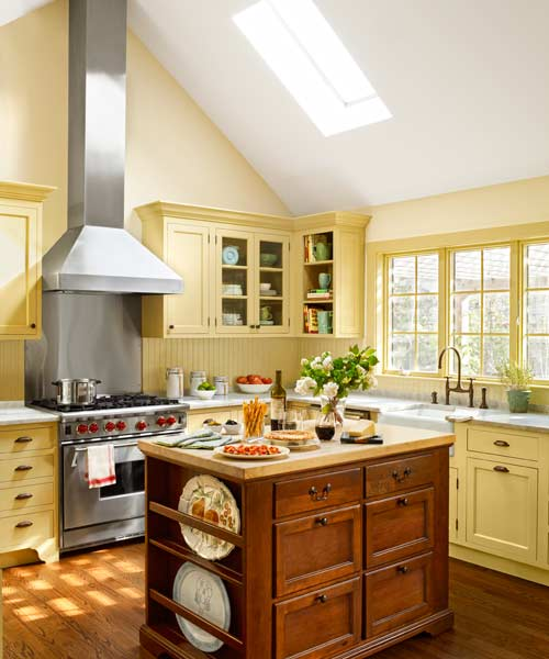yellow traditional kitchen with antique island, beadboard backsplash, marble counter, white apron sink