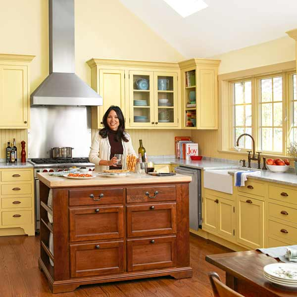 homeowner at antique kitchen island after yellow kitchen remodel