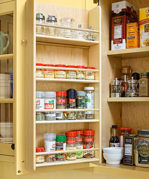 custom spice rack inside cabinet door after yellow kitchen remodel