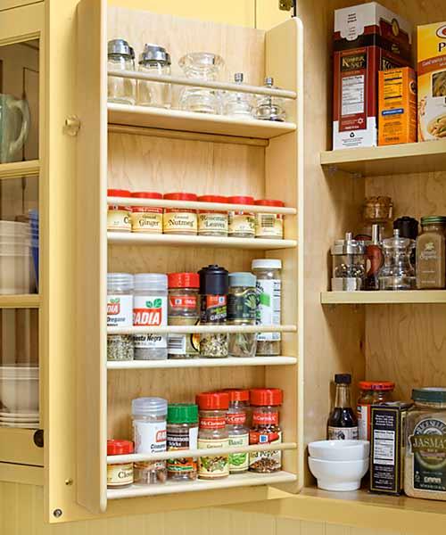custom spice rack inside cabinet door after yellow kitchen remodel