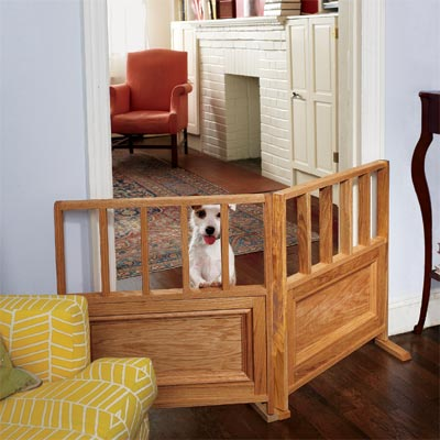 small dog standing up behind a pet-friendly interior wooden gate