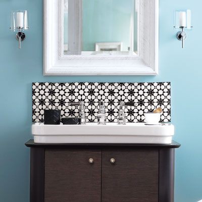 bathroom sink area with graphic backsplash