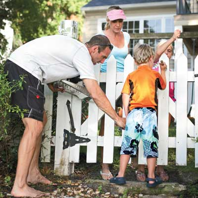 Rader family paints the picket fence in the front yard of their Orlando colonial home