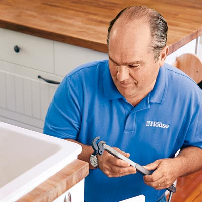 Richard Trethewey using a basin wrench inside a sink cabinet