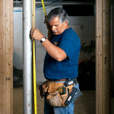 Tom Silva measures a lally-column with his custom tool belt on